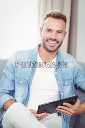 portrait of young man holding digital