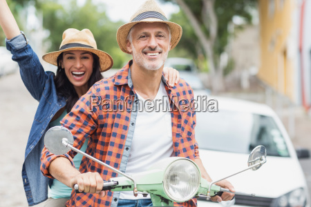 portrait of man riding moped with