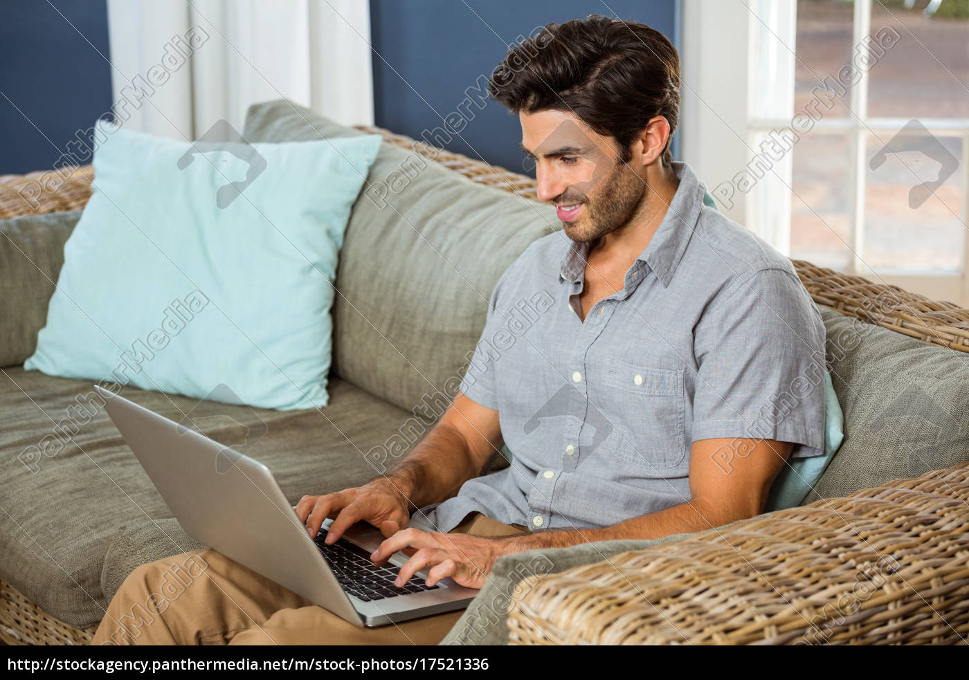 young, man, using, laptop, in, living - 17521336