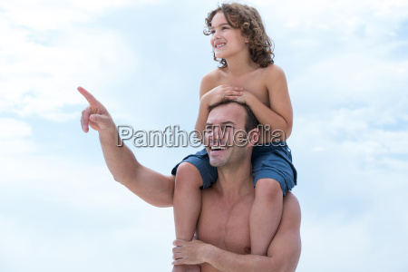 father carrying son on shoulder while