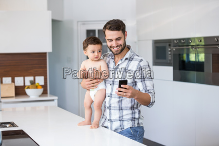 father using mobile phone while holding