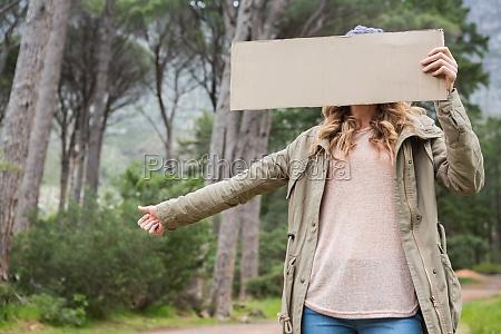 hitch hiking woman holding cardboard