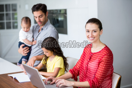 smiling mother working on laptop with