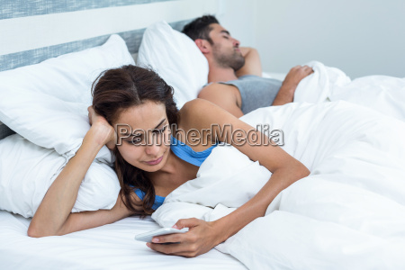 woman using phone while relaxing on