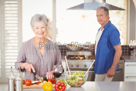 happy senior woman cutting vegetables with