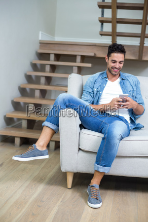 man using smartphone while sitting on