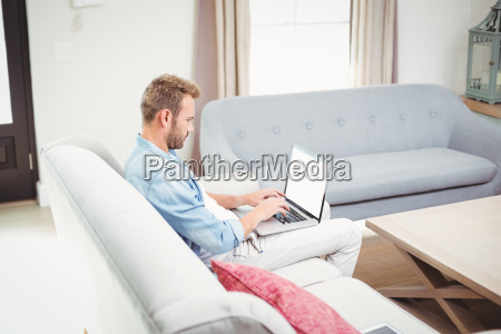 man using laptop while sitting on