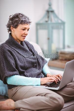 mature woman using laptop while sitting