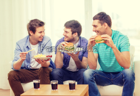 smiling friends with soda and hamburgers