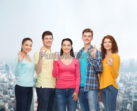 group of smiling teenagers over city