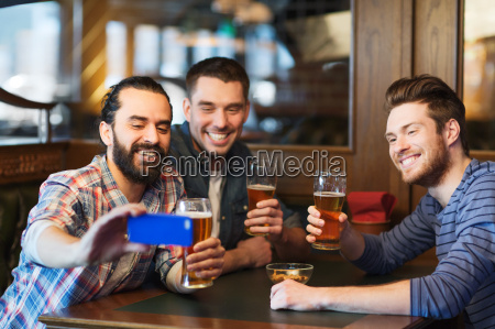male friends with smartphone drinking beer