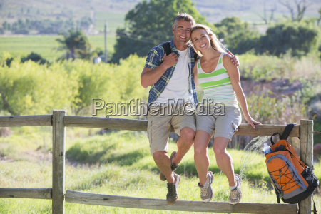 couple resting on a fence in