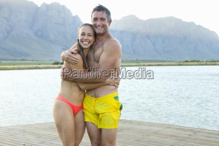 couple in swimwear on wooden jetty