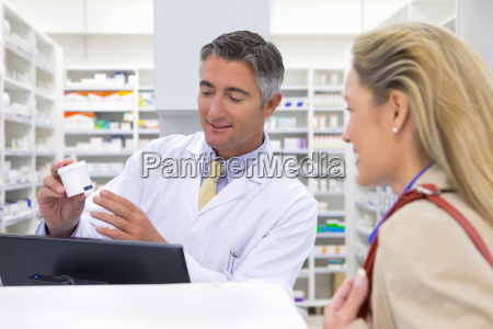 pharmacist showing customer medication from behind