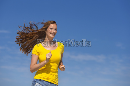 smiling woman running with blue sky