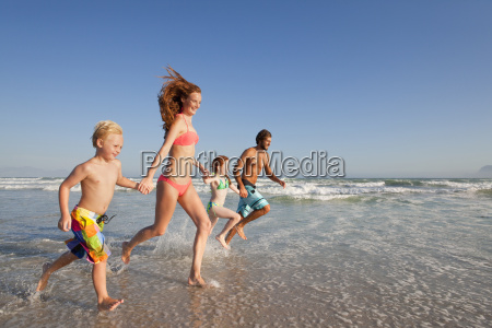 happy family running through water whilst