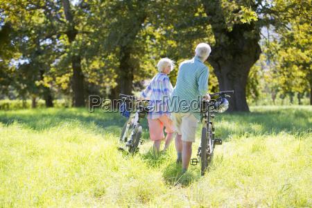 senior couple pushing mountain bikes in