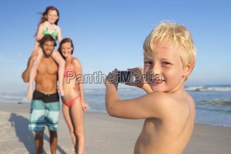 boy smiling at camera taking photo