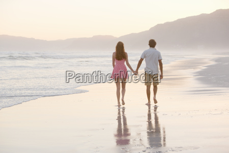 couple walking into distance holding hands