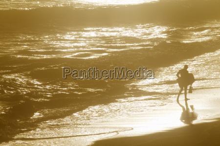man holding body board walking along