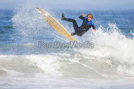 surfer mid air falling off surfboard