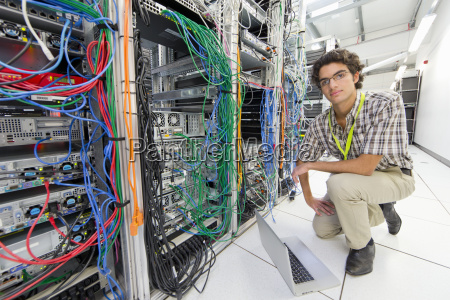 technician kneeling and looking at camera