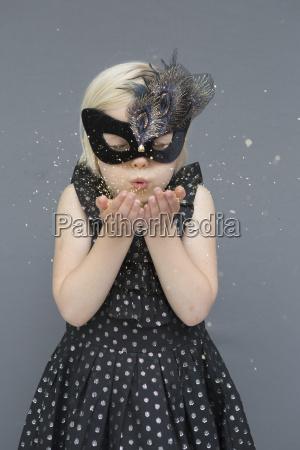 girl wearing masquerade mask blowing glitters