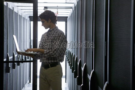 technician with laptop checking aisle of