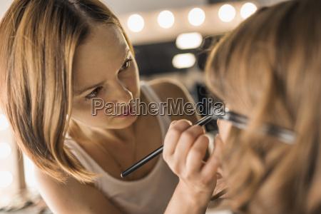 artist applying make up on fashion