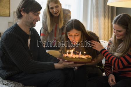 family looking at young woman blowing