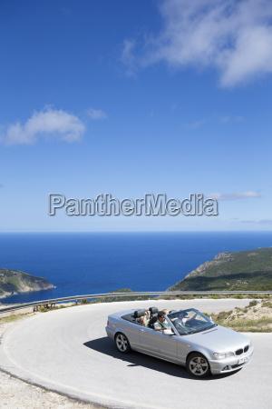 family driving convertible car along winding