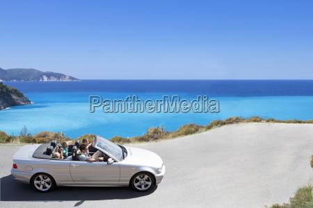 family driving convertible car along coastal