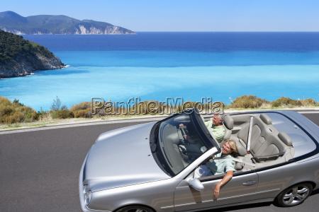 senior couple driving convertible car along