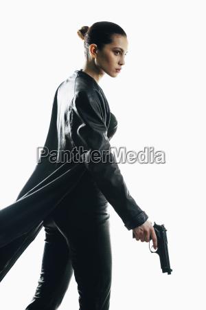 furious spy holding gun walking against