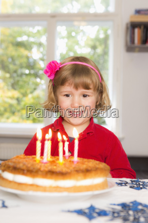 happy girl looking at birthday cake