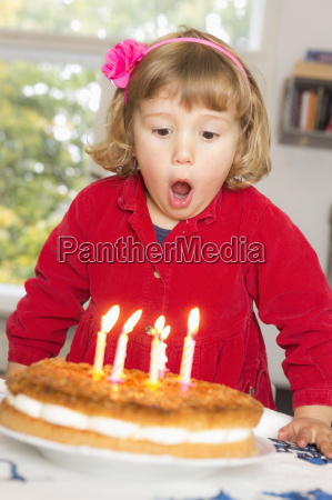 cute girl blowing birthday candles at