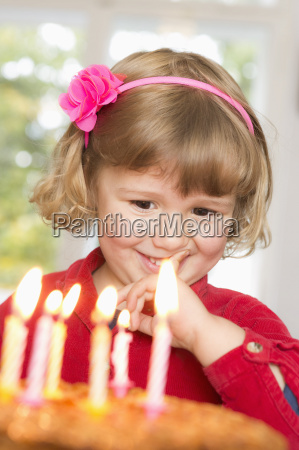 cute girl looking at birthday cake