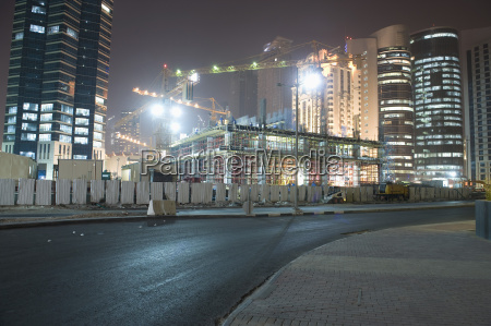 street against illuminated construction site and