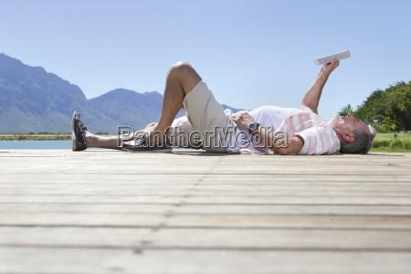 senior man lying on jetty reading