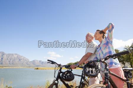 senior couple mountain biking on country