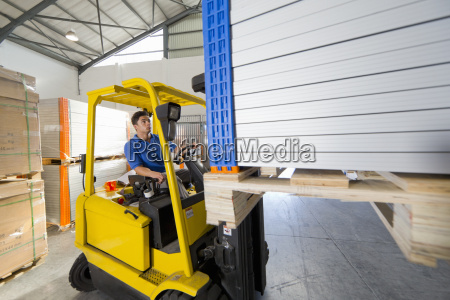 forklift truck driver worker stacking panels