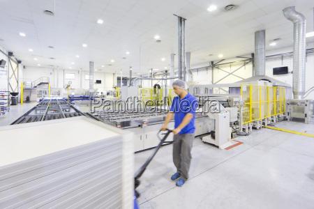 worker pulling pallet of solar panels
