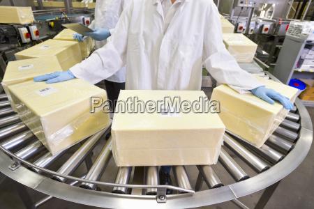 worker handling large blocks of cheese