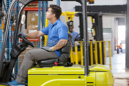 worker driving forklift stacking boxes in