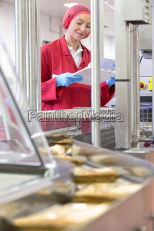 worker with clipboard at production line