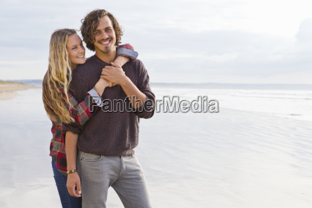 portrait smiling couple hugging on sunny