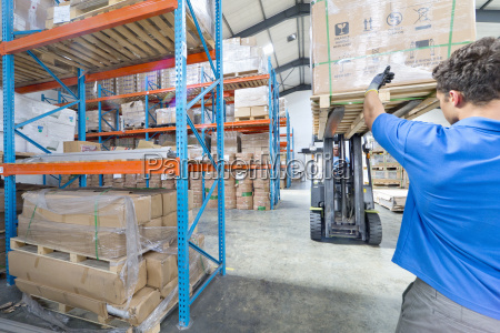 worker directing forklift truck in factory