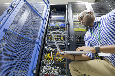 technician with laptop checking server in