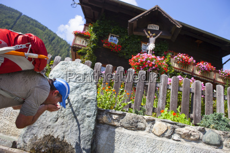 a male hiker drinks water from