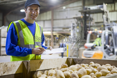 portrait confident worker with clipboard at